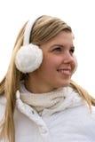 Ragazza sorridente nei manicotti dell'orecchio della cuffia avricolare Fotografia Stock