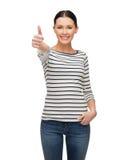 Ragazza sorridente nel clother casuale che mostra i pollici su Immagini Stock Libere da Diritti