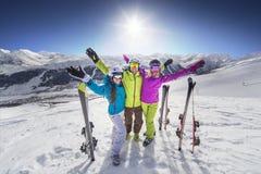 Ragazza sorridente nella località di soggiorno delle alpi di corsa con gli sci della giacca blu Immagine Stock