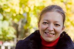 Ragazza sorridente nella sosta di autunno Immagini Stock Libere da Diritti