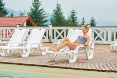 Ragazza sorridente sexy che si trova sulla chaise-lounge bianca con l'asciugamano immagini stock libere da diritti