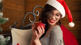 Ragazza sorridente sexy nella palla di natale della tenuta del cappello del Babbo Natale archivi video