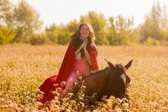 ragazza sorridente su un cavallo in un mantello immagini stock