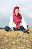 Ragazza sorridente su una pila di paglia Fotografie Stock