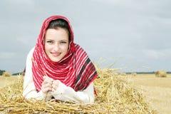 Ragazza sorridente su una pila di paglia Fotografie Stock Libere da Diritti