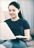 Ragazza sorridente sul sofà con il computer portatile fotografie stock
