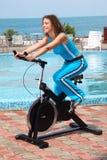 Ragazza sorridente sull'apparecchiatura di addestramento della bicicletta esterna fotografie stock libere da diritti