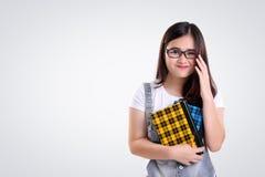 Ragazza sorridente sveglia con i vetri del nerd su bianco Immagini Stock Libere da Diritti