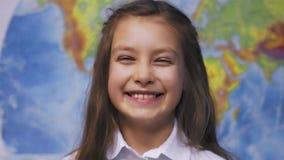 Ragazza sorridente sveglia del bambino in camicia bianca a scuola stock footage