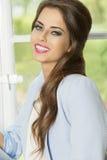Ragazza sorridente vicino alla finestra Fotografie Stock