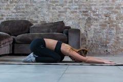 Ragazza sottile che fa indietro allungamento dell'esercizio che sta nella posa di preghiera su yoga di pratica del pavimento a ca Fotografie Stock Libere da Diritti