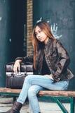 Ragazza splendida che posa con la borsa di cuoio, stile dei pantaloni a vita bassa Fotografie Stock