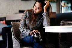 Ragazza splendida che si siede su una sedia piacevole con la macchina fotografica della foto in sue mani Fotografie Stock Libere da Diritti