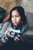 Ragazza splendida che si trova sul sofà di cuoio con la macchina fotografica della foto in sue mani Fotografie Stock Libere da Diritti
