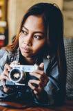 Ragazza splendida che si trova sul sofà di cuoio con la macchina fotografica della foto in sue mani Immagini Stock