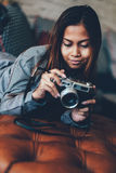 Ragazza splendida che si trova sul sofà di cuoio con la macchina fotografica della foto in sue mani Fotografia Stock Libera da Diritti