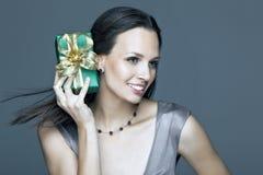 Ragazza splendida che tiene un regalo in sue mani Fotografia Stock