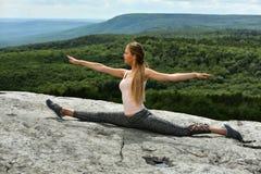Ragazza sportiva che fa allungamento sulla cima della montagna Fotografie Stock