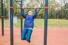 Ragazza sportiva che fa esercizio di Tirata-UPS alla palestra all'aperto fotografia stock