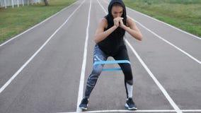 Ragazza sportiva che fa gli esercizi di gamba con l'elastico di forma fisica stock footage
