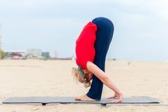 Ragazza sportiva che fa Headstand di sostegno, asana Uttanasana di yoga sul fondo della costa Immagini Stock Libere da Diritti