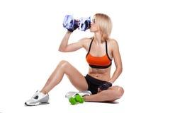 Ragazza sportiva che si siede sul pavimento, acqua potabile fotografia stock