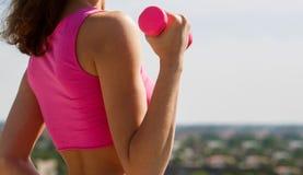 Ragazza sportiva dumbbell Muscoli d'esercitazione femminili misura Ragazza di forma fisica di sport Muscoli con la testa di legno fotografia stock libera da diritti