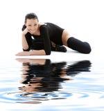 Ragazza sportiva in leotard nero sulla sabbia bianca Fotografia Stock