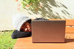 Ragazza stanca che lavora al taccuino Fotografie Stock