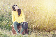 Ragazza stanca con il cappello che si siede e che riposa sulla valigia d'annata marrone nella strada del campo durante il tramont Fotografia Stock