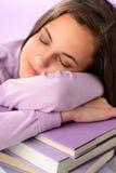 Ragazza stanca dello studente che dorme sui libri porpora Fotografia Stock Libera da Diritti