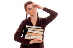 Ragazza stanca dello studente in vestiti marroni di sport con molti libri in sua una mano ed in secondo luogo sulla sua posa dell Fotografie Stock Libere da Diritti