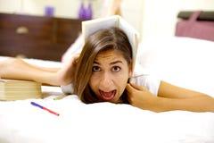 Ragazza stanca di studio dei grida con il libro sulla testa Immagini Stock