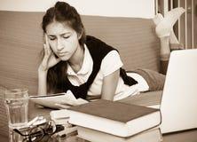 Ragazza stanca dietro il suo computer portatile Fotografie Stock