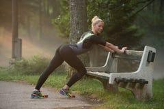 Ragazza Streching le sue gambe prima di correre all'aperto Immagine Stock Libera da Diritti