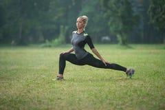 Ragazza Streching le sue gambe prima di correre all'aperto Immagini Stock