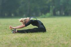 Ragazza Streching le sue gambe prima di correre all'aperto Fotografia Stock Libera da Diritti
