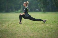 Ragazza Streching le sue gambe prima di correre all'aperto Immagini Stock Libere da Diritti