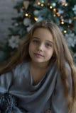 Ragazza stupefacente bella sui precedenti dell'albero di Natale Fotografia Stock Libera da Diritti