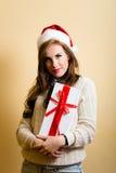 Ragazza stupefacente dei pantaloni a vita bassa in cappello di Santa che tiene a Immagine Stock Libera da Diritti