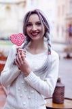 Ragazza stupefacente del ritratto del primo piano nel maglione di lana caldo bianco con capelli d'argento grigi con la lecca-lecc Immagine Stock