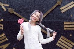 Ragazza stupefacente del ritratto del primo piano nel maglione di lana caldo bianco con capelli d'argento grigi con la lecca-lecc Fotografia Stock