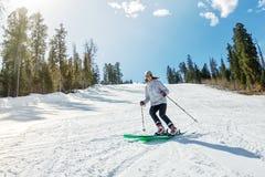 Ragazza su sci alpino su una pista nevosa contro il cielo Fotografie Stock Libere da Diritti
