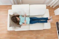 Ragazza su Sofa Using Digital Tablet fotografie stock libere da diritti