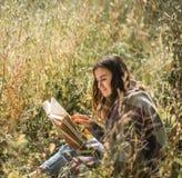 Ragazza su un campo che legge un libro Immagini Stock Libere da Diritti