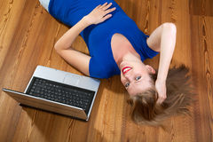 Ragazza su un pavimento di legno con un computer portatile Immagine Stock
