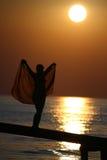 Ragazza su un ponticello all'insieme del sole. Fotografia Stock