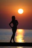 Ragazza su un ponticello all'insieme del sole. Fotografia Stock Libera da Diritti