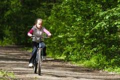 Ragazza su una bici nella foresta fotografie stock