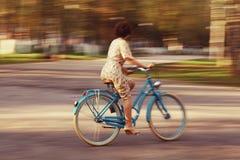Ragazza su una bicicletta nel movimento Immagini Stock